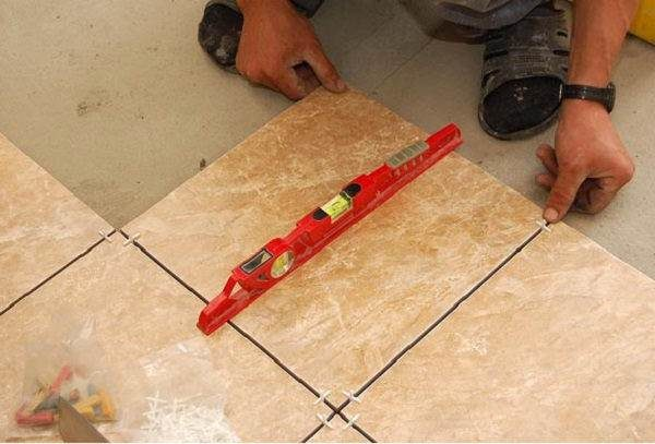 Проверка ровности укладки напольной плитки уровнем